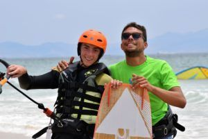 Alumno e instructor con kite y tabla de kitesurf en las playas de Tarifa